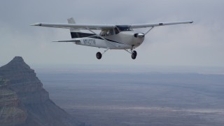 AX139_123 - Aerial stock footage of Tracking Cessna flying high above desert, near mountains, Emery County, Utah