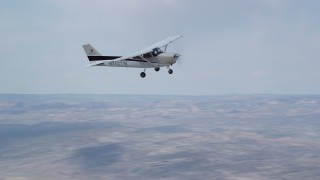 AX139_125 - Aerial stock footage of Tracking Cessna flying high above desert, partly cloudy, Emery County, Utah