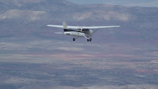 AX139_126 - Aerial stock footage of Tracking Cessna flying high above desert, partly cloudy, Emery County, Utah
