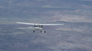 AX139_127 - Aerial stock footage of Tracking Cessna flying high above desert, partly cloudy, Emery County, Utah