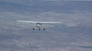 AX139_128 - Aerial stock footage of Tracking Cessna flying high above desert, partly cloudy, Emery County, Utah
