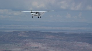 AX139_130 - Aerial stock footage of Tracking Cessna high above desert, descend out of frame, Emery County, Utah