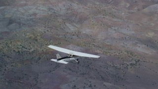 AX139_131 - Aerial stock footage of Tracking Cessna flying high above desert, Emery County, Utah
