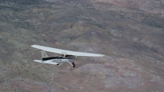 AX139_132 - Aerial stock footage of Tracking Cessna flying high above desert, partly cloudy, Emery County, Utah