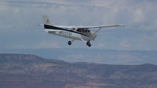 AX139_133 - Aerial stock footage of Tracking Cessna flying high above desert, ascend out of frame, Emery County, Utah