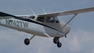 AX139_136 - Aerial stock footage of Tracking Cessna flying high above desert, closeup of cockpit, Emery County, Utah