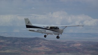 AX139_137 - Aerial stock footage of Tracking Cessna flying high above desert, partly cloudy, Emery County, Utah