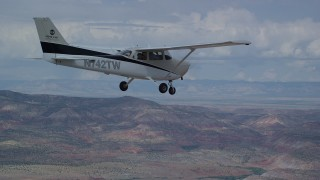 AX139_138 - Aerial stock footage of Tracking Cessna flying high above desert, partly cloudy, Emery County, Utah