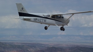 AX139_139 - Aerial stock footage of Zoom out from tail, tracking Cessna over desert, Emery County, Utah