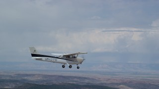 AX139_140 - 6K stock footage aerial video of tracking a Cessna flying over desert mountains, partly cloudy, Carbon County, Utah