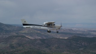 AX139_141 - 6K stock footage aerial video fly beside a Cessna over desert mountains, partly cloudy, Carbon County, Utah