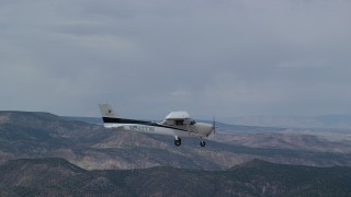 AX139_142 - 6K stock footage aerial video fly beside a Cessna in flight over desert mountains, partly cloudy, Carbon County, Utah