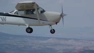 AX139_145 - 6K stock footage aerial video of flying beside a Cessna over desert mountains, closeup on cockpit, Carbon County, Utah