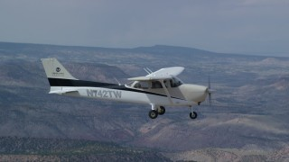 AX139_146 - 6K stock footage aerial video in flight beside a Cessna over desert mountains, partly cloudy, Carbon County, Utah