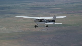 AX139_148 - 6K stock footage aerial video of tracking Cessna flying over desert, reveal distant mountains, Carbon County, Utah