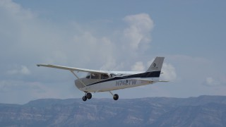 AX139_149 - 6K stock footage aerial video track a Cessna aircraft flying over desert, mountains in distance, Carbon County, Utah