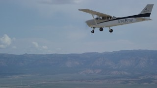 AX139_150 - 6K stock footage aerial video of a Cessna plane flying over desert, mountains in distance, Carbon County, Utah