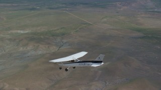 AX139_151 - 6K stock footage aerial video track a Cessna flying over desert, ascend to bird's eye view of plane, Carbon County, Utah