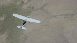 AX139_155 - 6K stock footage aerial video of a bird's eye view of a Cessna flying over open desert, Carbon County, Utah