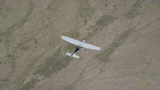 AX139_156 - 6K stock footage aerial video of a bird's eye view of a Cessna in flight over desert, Carbon County, Utah