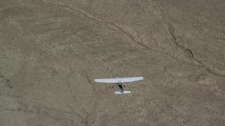 AX139_157 - 6K stock footage aerial video of a bird's eye of a Cessna plane in flight high over desert, Carbon County, Utah