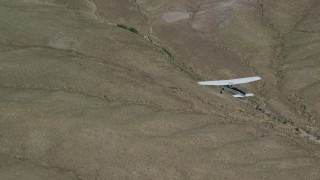 AX139_158 - 6K stock footage aerial video of a bird's eye view of a Cessna flying over desert landscape, Carbon County, Utah