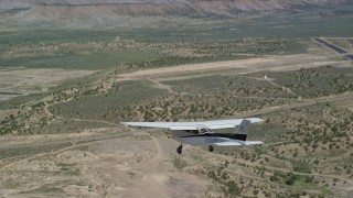AX139_159 - 6K stock footage aerial video of tracking a Cessna flying over desert near airport, Buck Davis Field, Utah