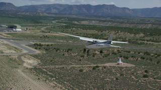 AX139_162 - 6K stock footage aerial video of tracking a Cessna flying over desert and approaching Buck Davis Field, Utah