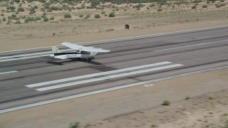 AX139_165 - 6K stock footage aerial video of tracking a Cessna slowing on runway after landing, Buck Davis Field, Utah