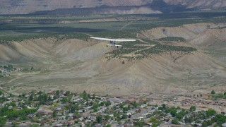 AX140_005 - 6K stock footage aerial video of tracking a Cessna over small town, approaching mesas, mountains, Price, Utah