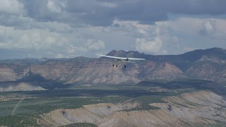 AX140_006 - 6K stock footage aerial video of tracking a Cessna airplane over desert, approaching distant mountains, Carbon County, Utah