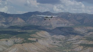 AX140_007 - 6K stock footage aerial video of a Cessna plane over desert, approaching distant mountains, Carbon County, Utah