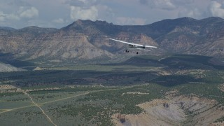 AX140_008 - 6K stock footage aerial video of a Cessna airplane over desert valley, partly cloudy, Carbon County, Utah