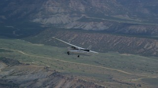 AX140_009 - 6K stock footage aerial video track a Cessna over desert, reveal mountains, Carbon County, Utah
