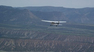 AX140_010 - 6K stock footage aerial video of a Cessna aircraft over desert, partly cloudy, distant mountains, Carbon County, Utah