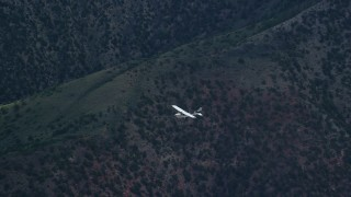 AX140_015 - 6K stock footage aerial video of a Cessna aircraft over desert mountains, zoom in tighter on the plane, Carbon County, Utah