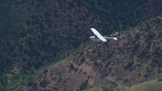 AX140_017 - 6K stock footage aerial video of a view of a Cessna airplane over desert mountains, zoom wider, Carbon County, Utah