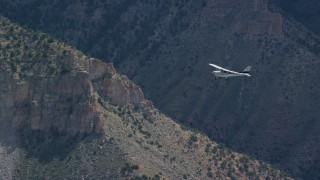AX140_018 - 6K stock footage aerial video of a Cessna in flight over desert mountains, Carbon County, Utah