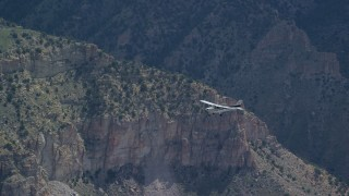 AX140_019 - 6K stock footage aerial video of a Cessna airplane in flight over desert mountains, Carbon County, Utah