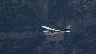 AX140_021 - 6K stock footage aerial video of flying near a Cessna over desert mountains, Carbon County, Utah