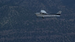 AX140_022 - 6K stock footage aerial video of Cessna over desert mountains and mountain road, Carbon County, Utah
