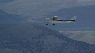 AX140_023 - 6K stock footage aerial video of a Cessna plane over desert mountains on partly cloudy day, Carbon County, Utah