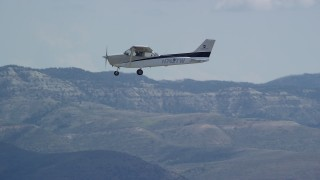 AX140_024 - 6K stock footage aerial video of tracking Cessna over desert mountains, partly cloudy day, Carbon County, Utah