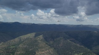 AX140_025 - 6K stock footage aerial video of a wide view of a Cessna over desert mountains, partly cloudy, Carbon County, Utah