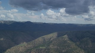 AX140_026 - 6K stock footage aerial video wide view of a Cessna over desert mountains, partly cloudy day, Carbon County, Utah