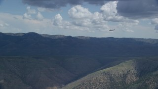 AX140_027 - 6K stock footage aerial video zooming in on a Cessna over desert mountains, partly cloudy day, Carbon County, Utah