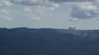 AX140_029 - 6K stock footage aerial video of a wide view of a Cessna aircraft over desert mountains, partly cloudy day, Carbon County, Utah