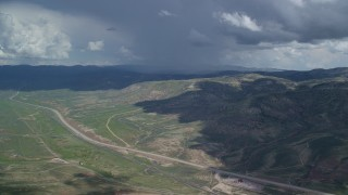 AX140_038 - 6K stock footage aerial video of a wide view of mountains and Highway 6, Colton ghost town, clouds, Wasatch Range, Utah County, Utah