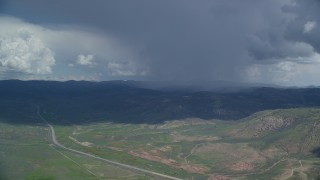 AX140_042 - 6K stock footage aerial video track a distant Tecnam P2006T by a rainstorm and Highway 6, Wasatch Range, Utah County, Utah