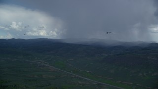 AX140_047 - 6K stock footage aerial video of tracking Tecnam P2006T and Cessna near rainstorm and Highway 6, Wasatch Range, Utah